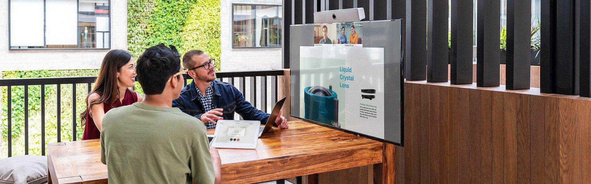 Drei Personen sitzen an Holztisch und schauen auf ein Display