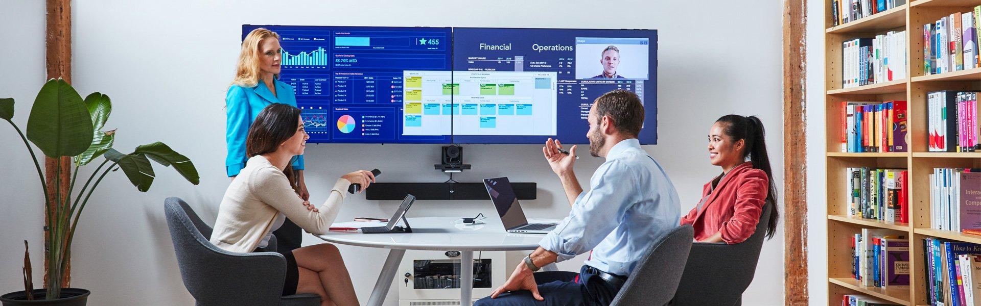 Oblong Mezzanine System mit zwei Displays in Sitzungszimmer mit vier Personen am Tisch die etwas miteinander besprechen