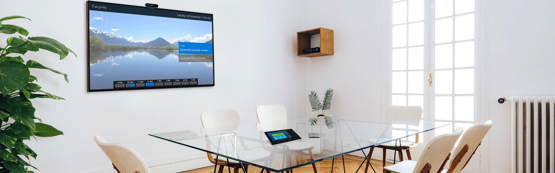 Modernes Sitzungszimmer mit Glastisch und weissen Stühlen und Display an der Wand