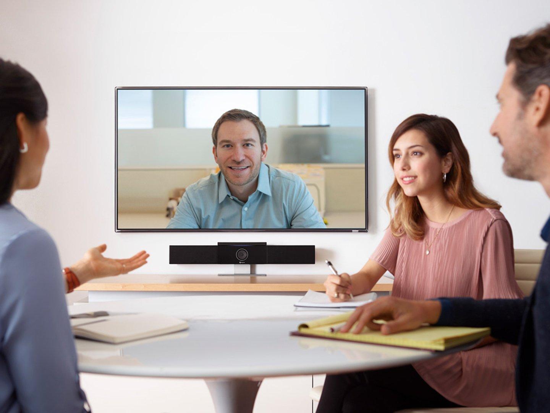 Display an Wand, drei Personen am Tisch die zusammen reden