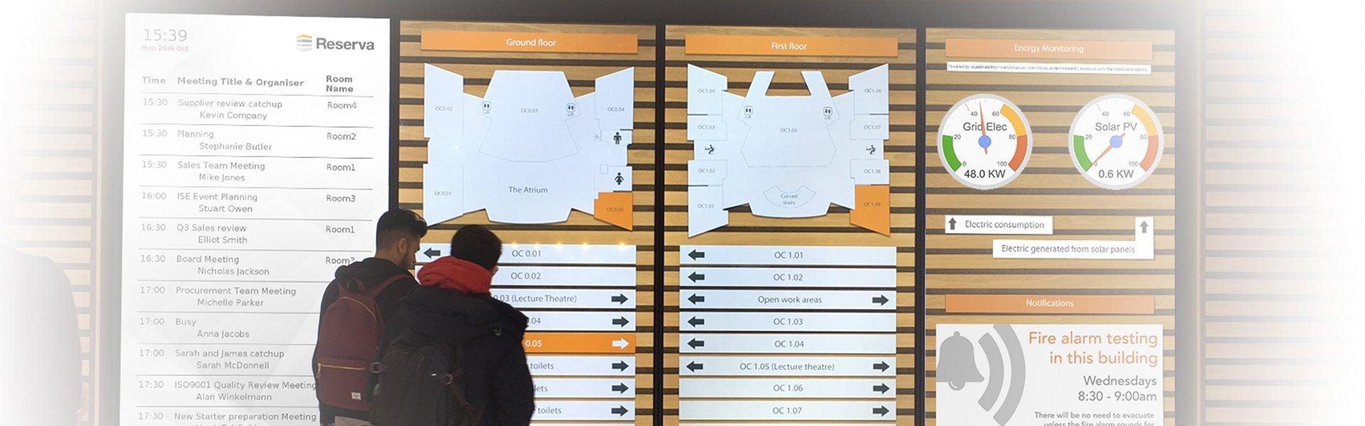 SlideVier grosse Displays an Wand und zwei Personen die vorne dran stehen und den Inhalt (Raumübersichtsplan) lesen