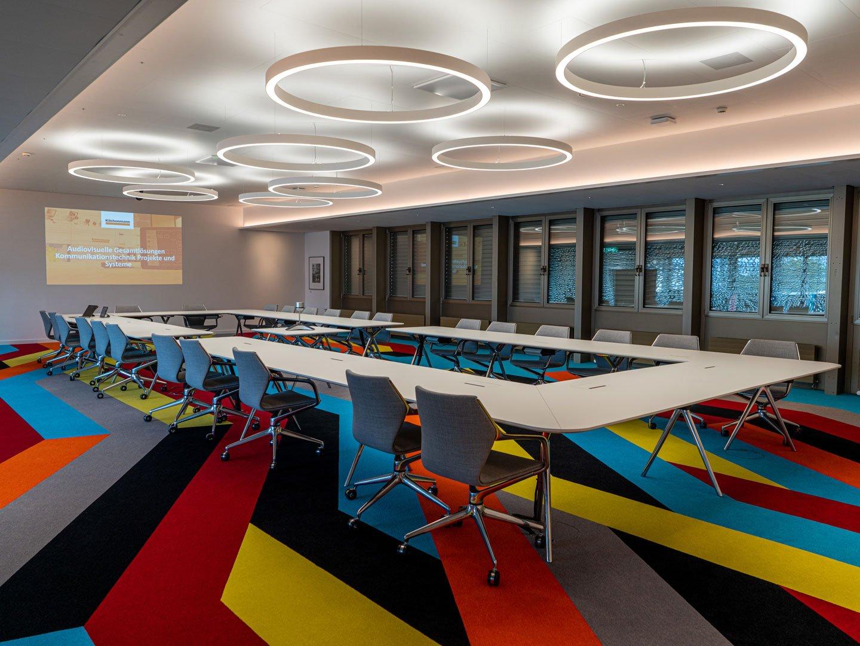 Referenzbild Mobiliar Innenraum mit einer Projektionswand und moderner Möblierung