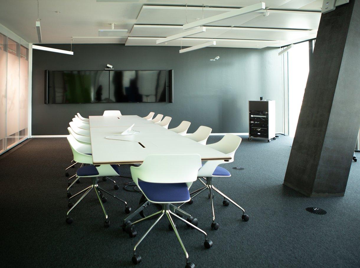Grosses Sitzungszimmer mit Tisch, Stühlen und zwei Displays