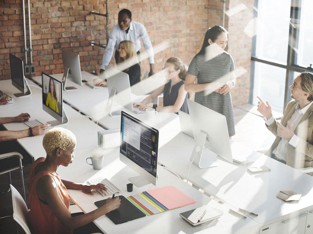 Viele Arbeitsplätze mit Menschen am Arbeiten vor ihren Bildschirmen