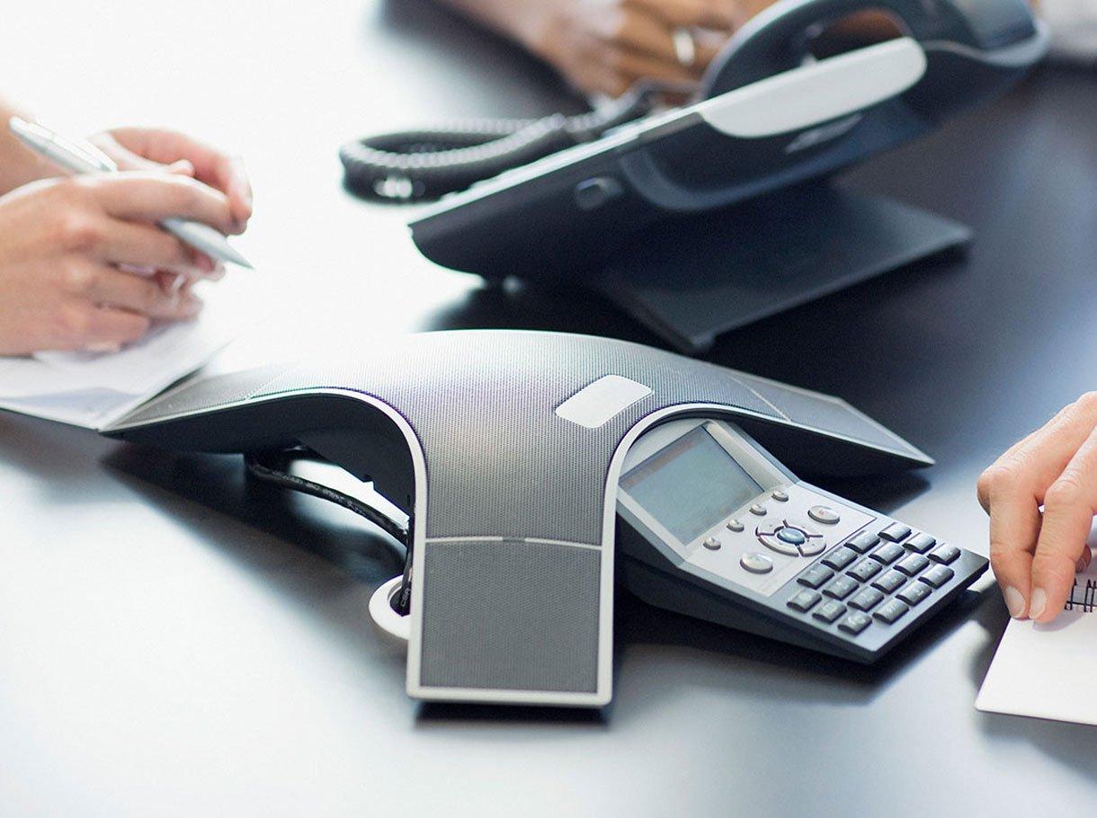 Telefonkonferenzsystem auf einem Tisch mit drei Personen daneben