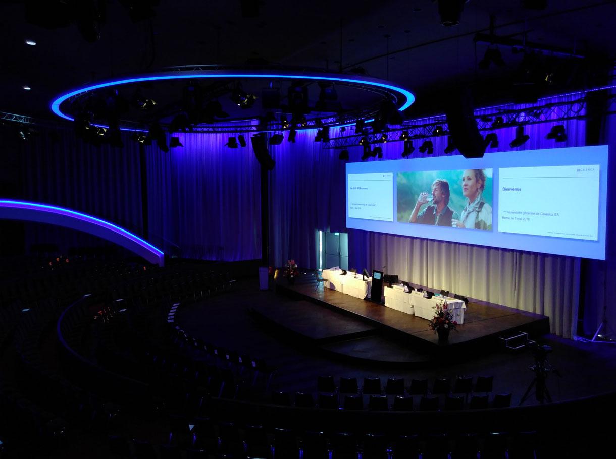 Grosser Höhrsaal mit beleuchteter Bühne auf der ein Podium steht und darüber eine grosse Leinwand mit drei Folien angezeigt wird