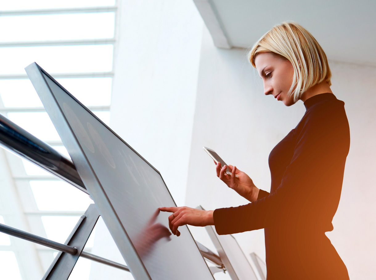 Eine Mitarbeiterin drückt auf einen Monitor mit Touchfunktion, der als Digital Signage-Lösung Informationen abbildet.